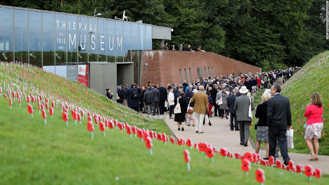 Visitors to the Thiepval Museum pass artificial poppies planted at the entrance to the museum with handwritten messages of commemoration to those who died at the Battle of the Somme.
