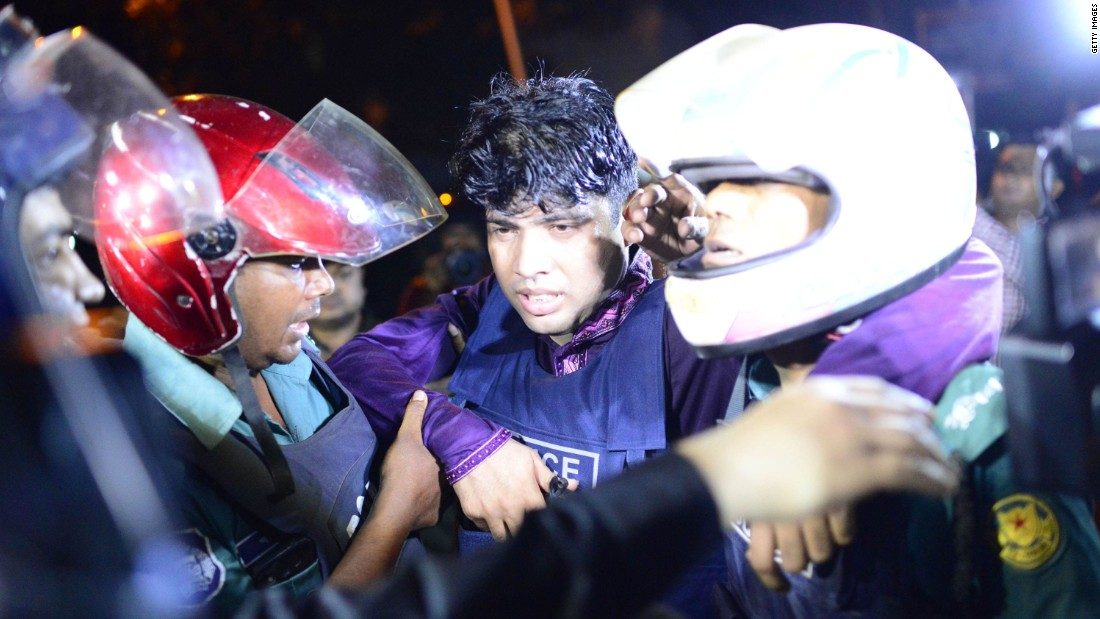 An injured police officer is led away after the cafe attack in the early hours of July 2 in Dhaka.