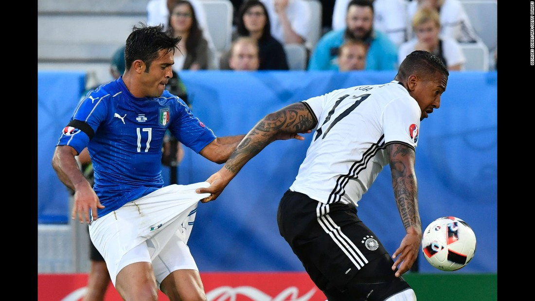 Germany defender Jerome Boateng, right, grabs the shorts of Italy forward Citadin Martins Eder while vying for the ball.