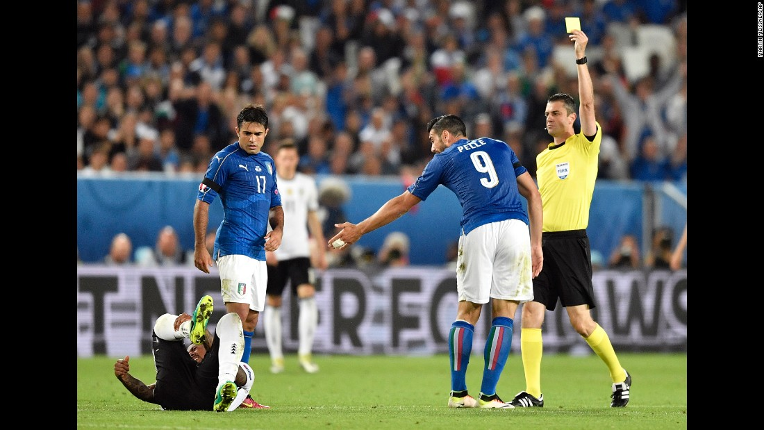 Referee Viktor Kassai shows a yellow card to Italy's Graziano Pelle. By the end of the match, Italy was given five yellow cards and Germany two.