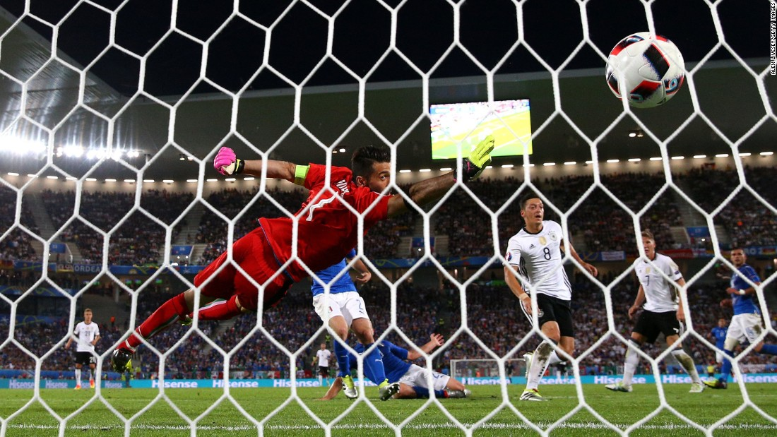 The ball flies past Gianluigi Buffon of Italy as he tries to block Mesut Oezil's opening goal.