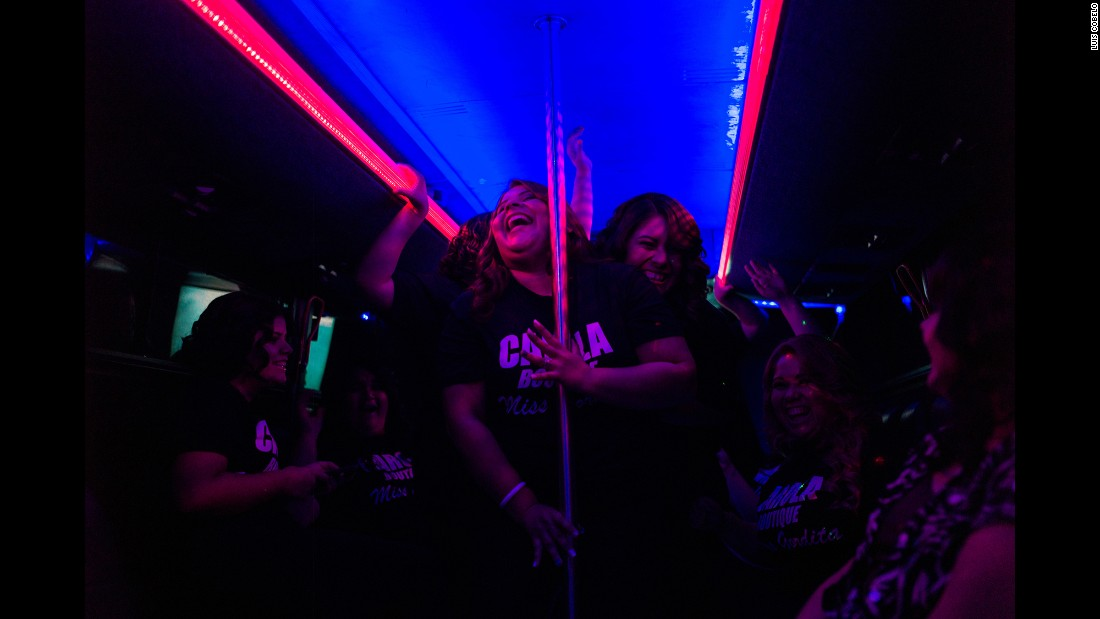 Mirley Espinosa, front, and Adelaida Anaquin dance on a bus as the contestants make their way to the pageant.