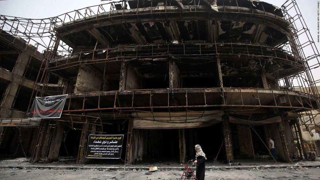 A woman walks by a building that was damaged in the Karrada blast.