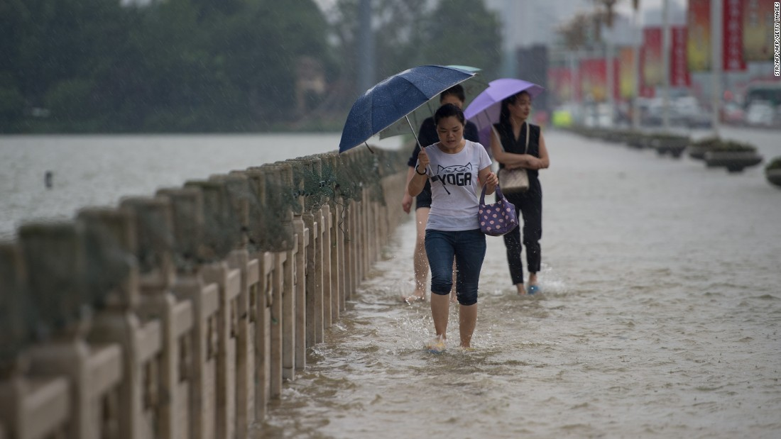 People cross a flooded bridge in Wuhan on July 2.