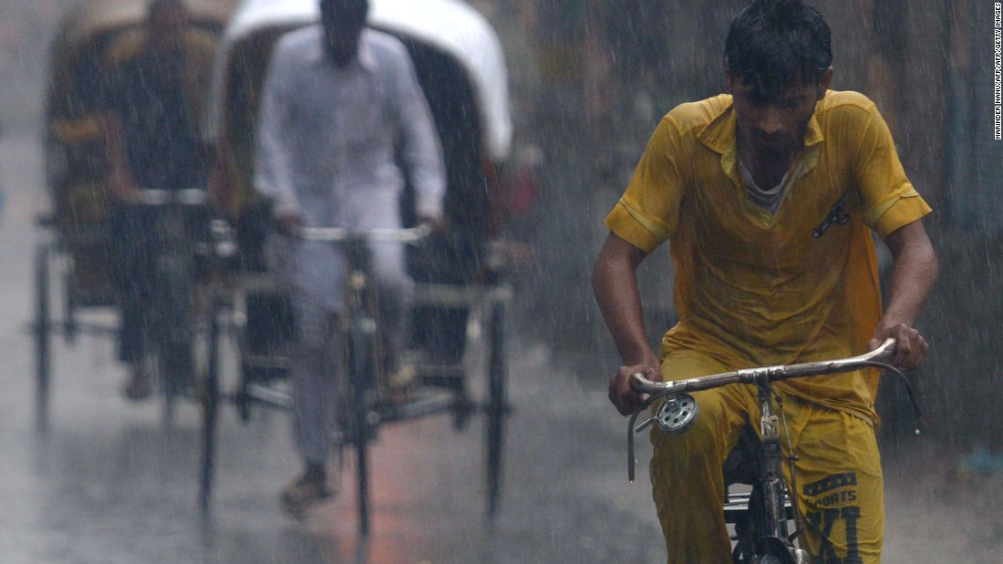 Indian commuters exposed to heavy monsoon rain in Amritsar while they bike down a water-logged road as flooding intensifies on July 3, 2016.