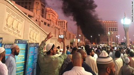 In this photo provided by Noor Punasiya, people stand by an explosion site in Medina, Saudi Arabia on July 4. State-linked Saudi news websites reported an explosion Monday near one of Islam's holiest sites in the city of Medina, as two suicide bombers struck in different cities. (Courtesy of Noor Punasiya via AP)