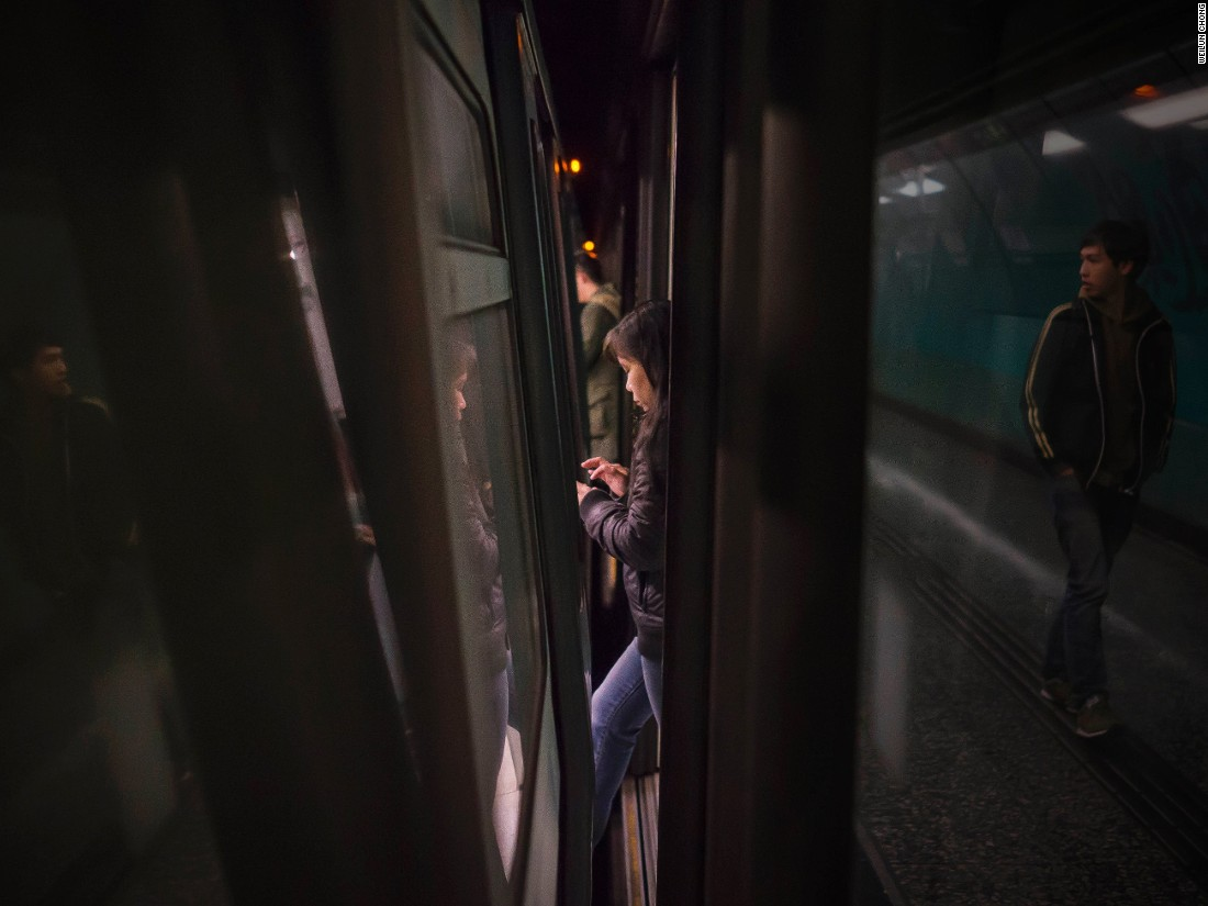 "Singapore-based photographer captured passengers as they moved through the narrow gaps between Hong Kong's subway trains and and platform doors. The compilation documents ""the hustle and bustle of Hong Kong,"" Chong says."
