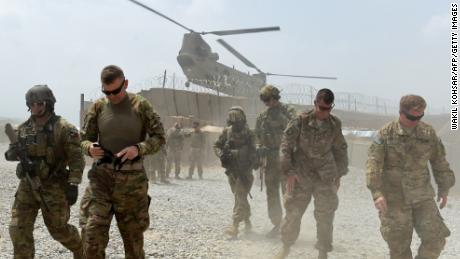 "In this photograph taken on August 13, 2015, US army soldiers walk as a NATO helicopter flies overhead at coalition force Forward Operating Base (FOB) Connelly in the Khogyani district in the eastern province of Nangarhar. From his watchtower in insurgency-wracked eastern Afghanistan, US army Specialist Josh Whitten doesn't have much to say about his Afghan colleagues. ""They don't come up here anymore, because they used to mess around with our stuff. ""Welcome to Forward Operating Base Connelly, where US troops are providing training and tactical advice to the 201st Afghan army corps as they take on the Taliban on the battlefield."