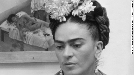 circa 1945:  Mexican painter Frida Kahlo (1907 - 1954) sits with her arms folded, looking down, in front of one of her paintings and a wooden bird cage. She wears flowers in her hair and a wooden necklace.  (Photo by Hulton Archive/Getty Images)