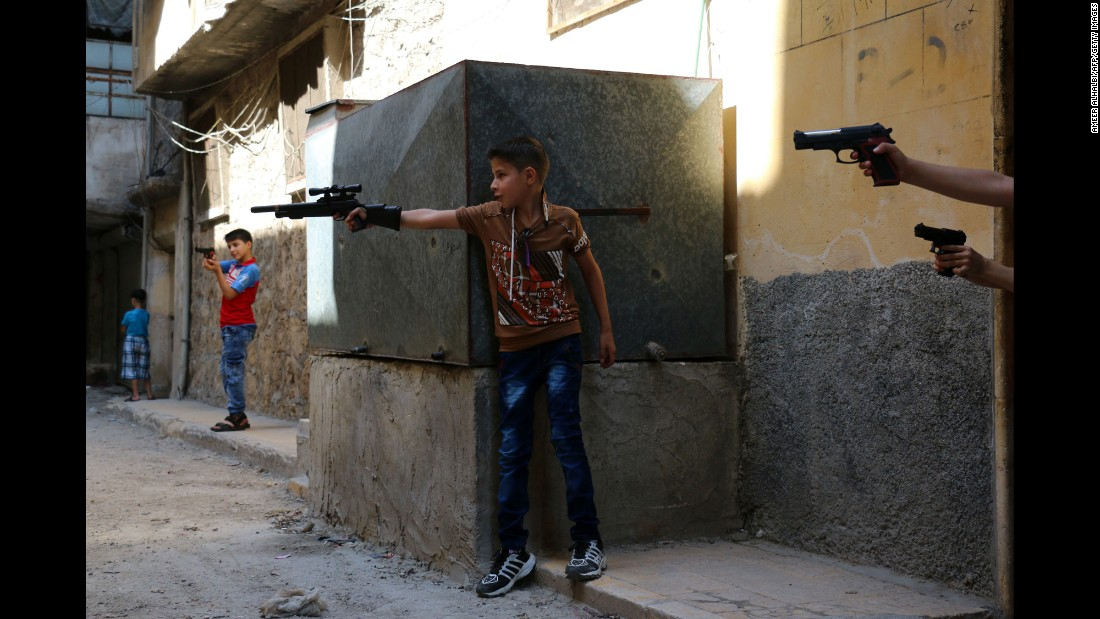 Children play with toy guns in a rebel-held district of Aleppo, Syria, on Wednesday, July 6.