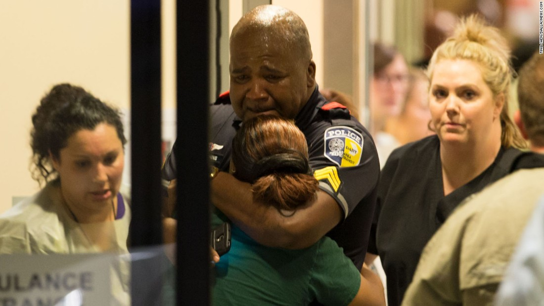 "A police officer with Dallas Area Rapid Transit is comforted at the emergency room entrance of the Baylor University Medical Center on Thursday, July 7. <a href=""http://www.cnn.com/2016/07/08/us/philando-castile-alton-sterling-protests/index.html"" target=""_blank"">Five police officers were fatally shot</a> during a protest over recent police shootings in Louisiana and Minnesota."