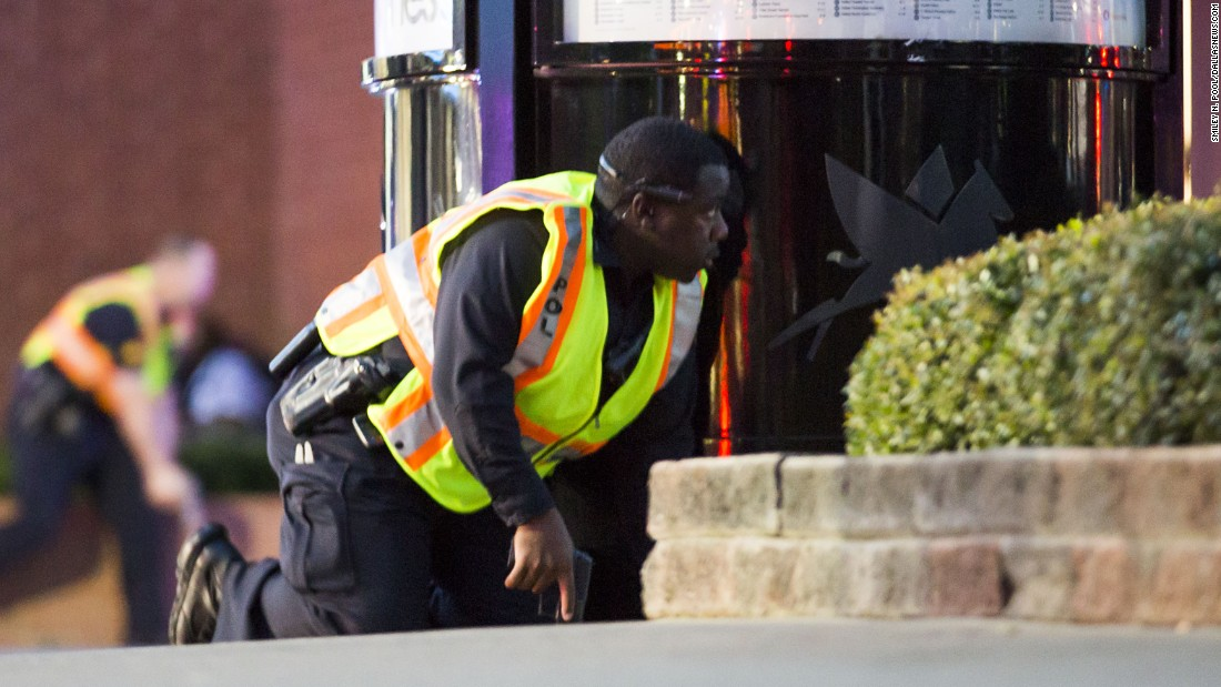Two officers crouch behind barriers.