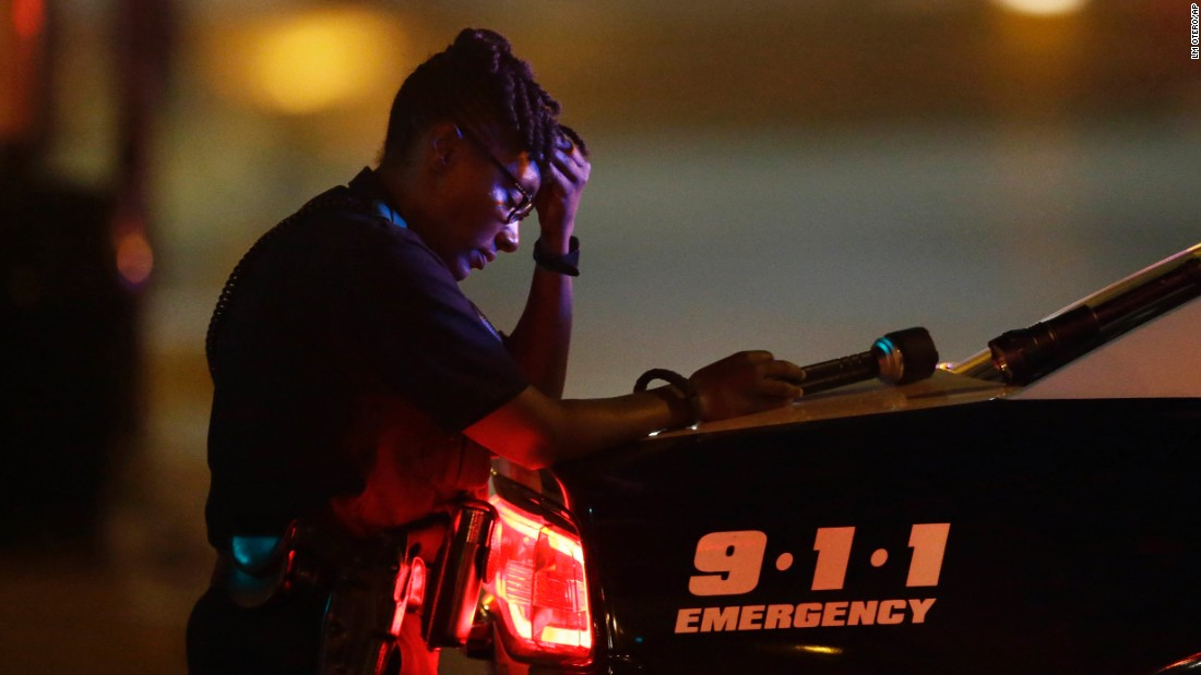A Dallas police officer takes a moment as she guards an intersection in the early morning hours.