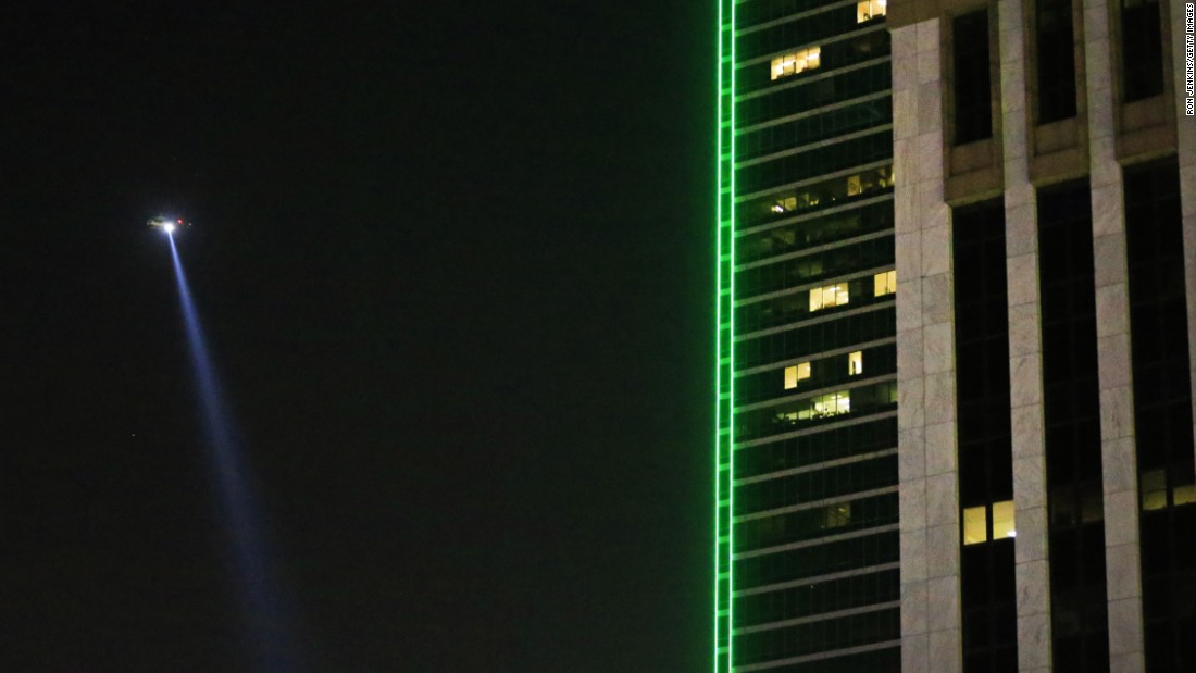 A police helicopter flies over the scene in downtown Dallas. One suspect was killed by police after a standoff that lasted for hours.