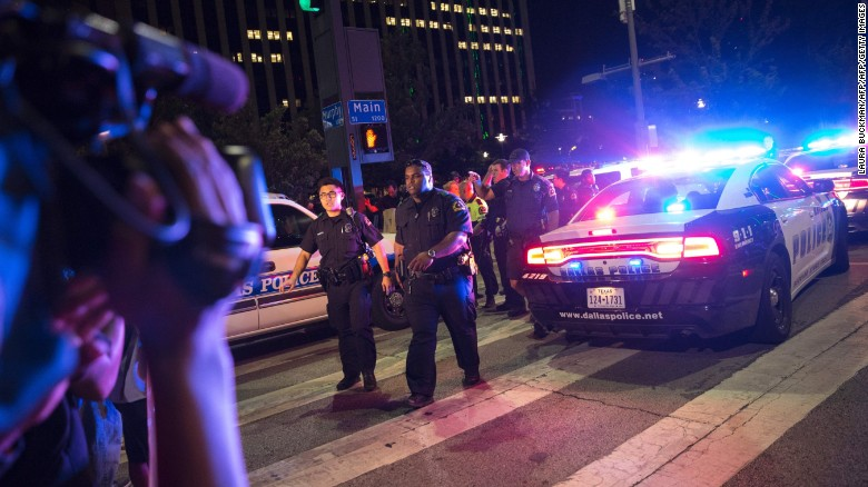 TOPSHOT - Bystanders stand near pollice baracades following the sniper shooting in Dallas on July 7, 2016.  A fourth police officer was killed and two suspected snipers were in custody after a protest late Thursday against police brutality in Dallas, authorities said. One suspect had turned himself in and another who was in a shootout with SWAT officers was also in custody, the Dallas Police Department tweeted.  / AFP / Laura Buckman        (Photo credit should read LAURA BUCKMAN/AFP/Getty Images)