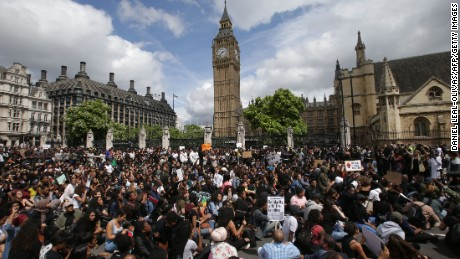 Demonstrators sit in the road on Parliament Square in central London on Sunda.