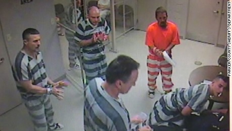 Inmates bust out of a holding cell to assist a corrections officer who experienced a medical emergency.