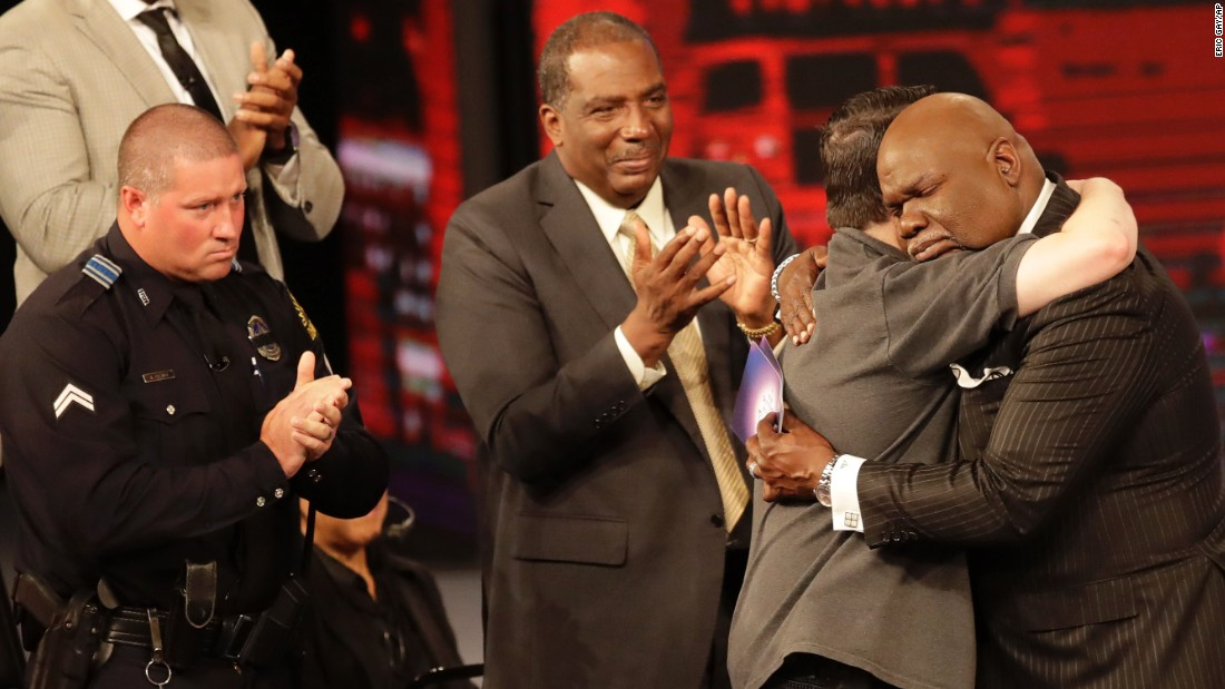 Bishop T.D. Jakes, hugs first responder during a service that included a memorial to the five officers killed in Dallas.