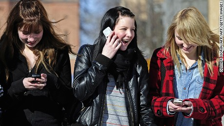 Teenagers use cell phones after school time in Vaasa on March 30, 2010.   AFP PHOTO OLIVIER MORIN. (Photo credit should read OLIVIER MORIN/AFP/Getty Images)
