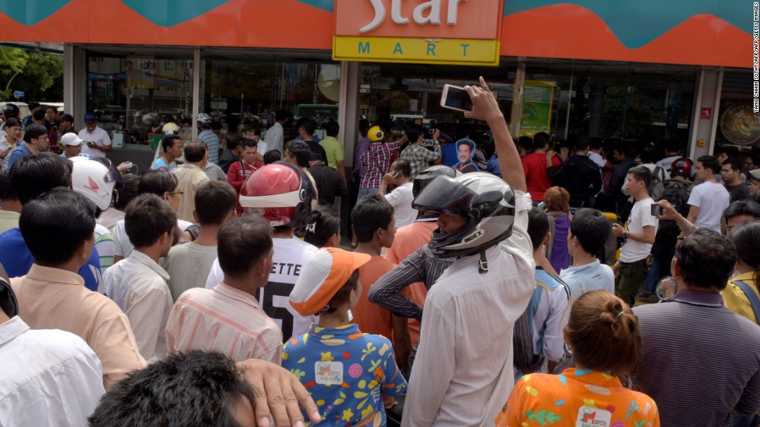Cambodian people gather outside a convenience store where Kem Ley was killed.