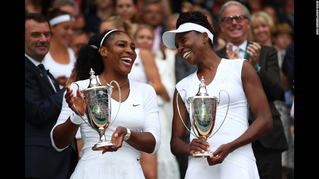 Venus and Serena Williams hold their trophies following their doubles victory over Timea Babos of Hungary and Yaroslava Shvedova of Kazakhstan on Day 12 of Wimbledon on Saturday, July 9.