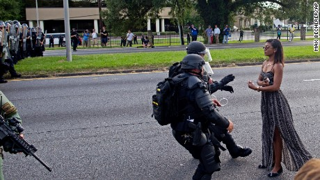 Riot police grab a protester after she refused to leave the road in Baton Rouge.