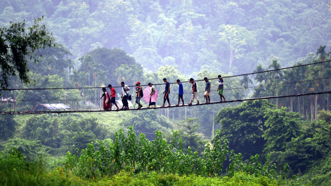 In the rural South Kamrup district, villagers from Meghalaya state cross a bridge over the Shree river to visit a weekly market in Ukiam.