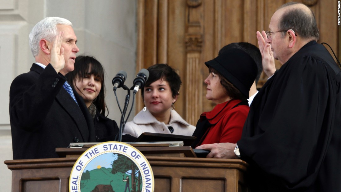 Pence is sworn in as Indiana's 50th governor by Chief Justin Brent E. Dickson as Pence's wife, Karen, and his family look on during a ceremony at the statehouse on January 14, 2013.