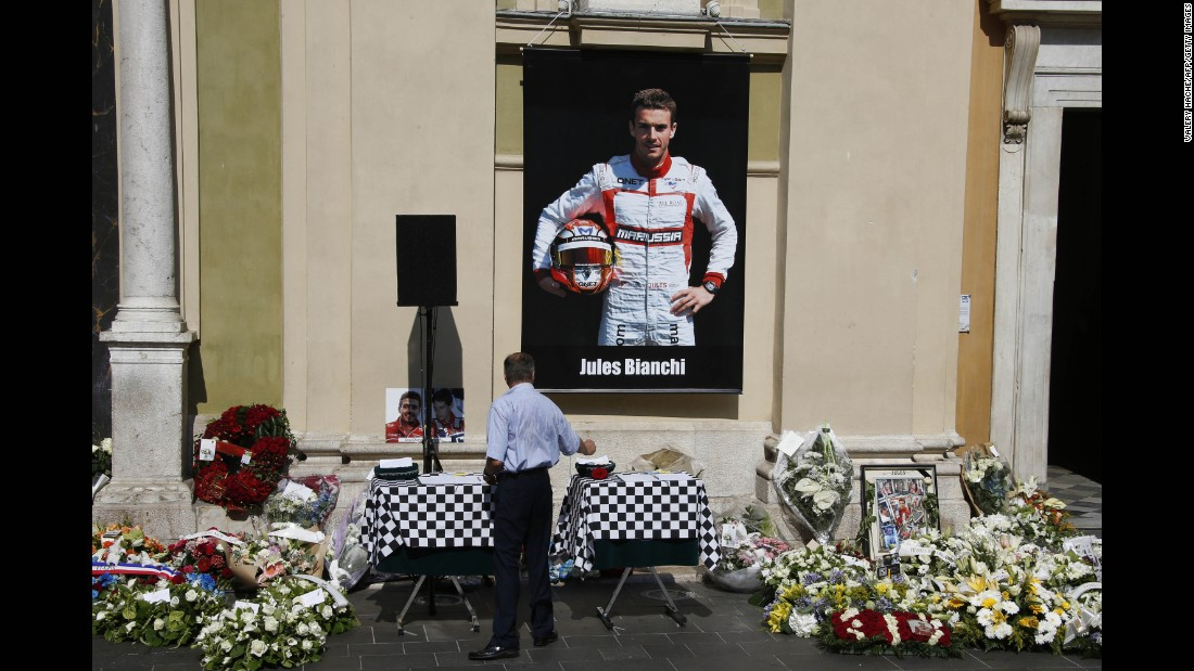 A man pays his respects below a poster showing Bianchi, after the driver's funeral ceremony at the Cathedrale Sainte Reparate in Nice on July 21, 2015, in southeastern France.