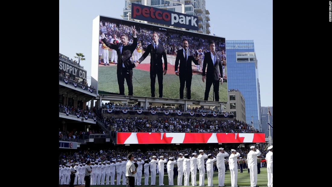 "The Tenors, shown on the scoreboard, perform the Canadian National Anthem before the MLB All-Star Game in San Diego on Tuesday, July 12. A member of the Canadian singing quartet changed a lyric in the anthem and held up a sign proclaiming ""All Lives Matter"" during a pregame performance."