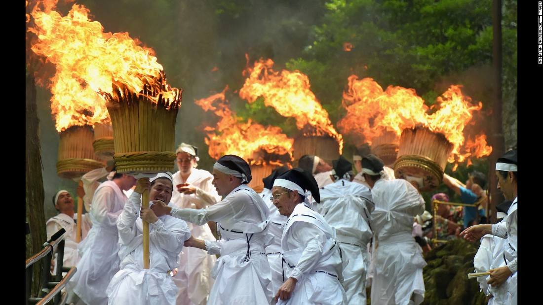 Shrine parishioners hold memorial torches to purify the path for portable shrines during the Kumano Nachi Fire Festival on Thursday, July 14, in Wakayama, Japan. The annual festival originated 1,500 years ago and attracts about 8,000 people.
