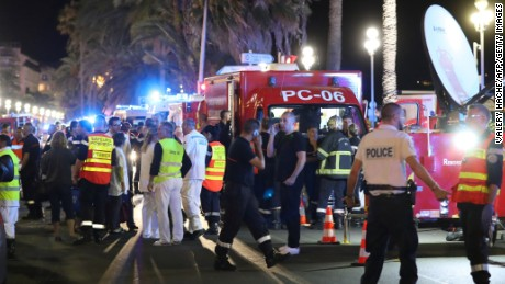"Police officers, firefighters and rescue workers are seen at the site of an attack on July 15, 2016, after a truck drove into a crowd watching a fireworks display in the French Riviera town of Nice. A truck ploughed into a crowd in the French resort of Nice on July 14, leaving at least 60 dead and scores injured in an ""attack"" after a Bastille Day fireworks display, prosecutors said on July 15."