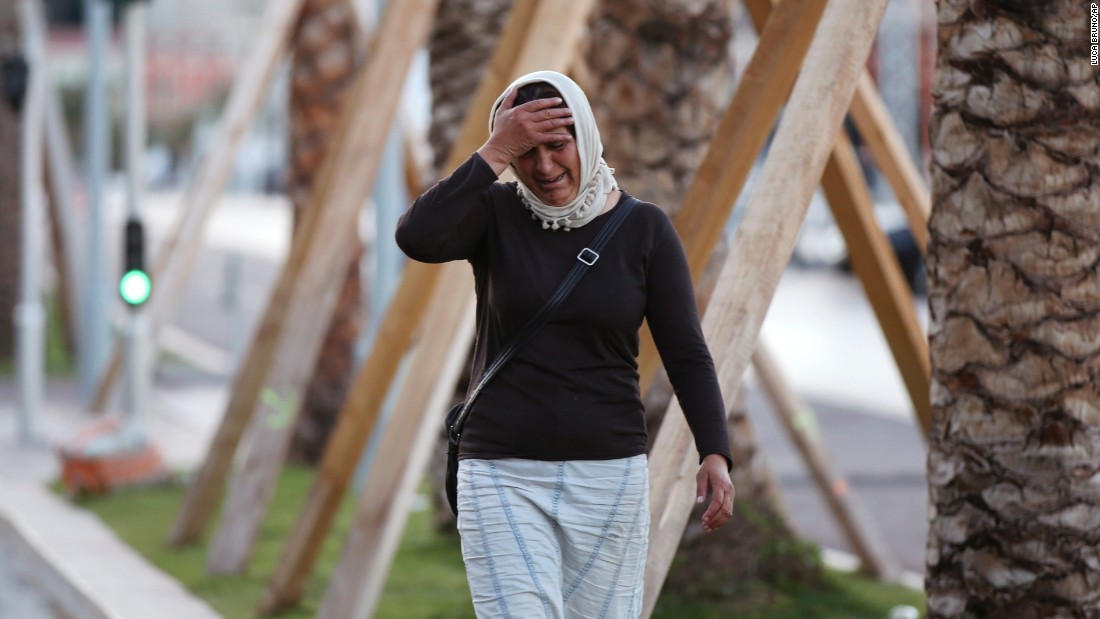 A woman cries, asking for her son, as she walks near the scene of the attack.