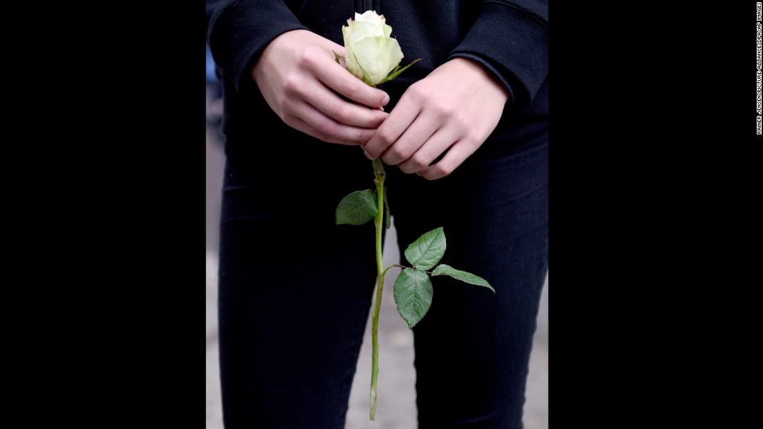 A pupil holds a white rose on the premises of the Paula Fuerst comprehensive school in Berlin, Germany.