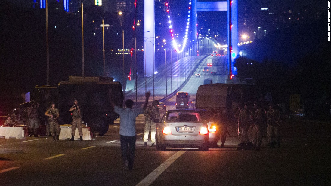 A man approaches Turkish military with his hands up at the entrance to the partially closed Bosphorus Bridge in Istanbul.