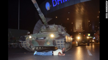 A man lays in front of a tank in the entrance to Istanbul's Ataturk airport, early Saturday, July 16, 2016. Members of Turkey's armed forces said they had taken control of the country, but Turkish officials said the coup attempt had been repelled early Saturday morning in a night of violence, according to state-run media. (Ismail Coskun/IHA via AP)
