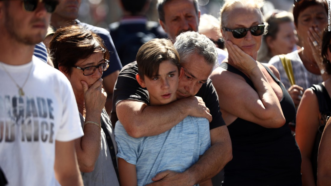 A boy is comforted as people gather and lay tributes on the Promenade des Anglais on Saturday, July 16 in Nice, France.