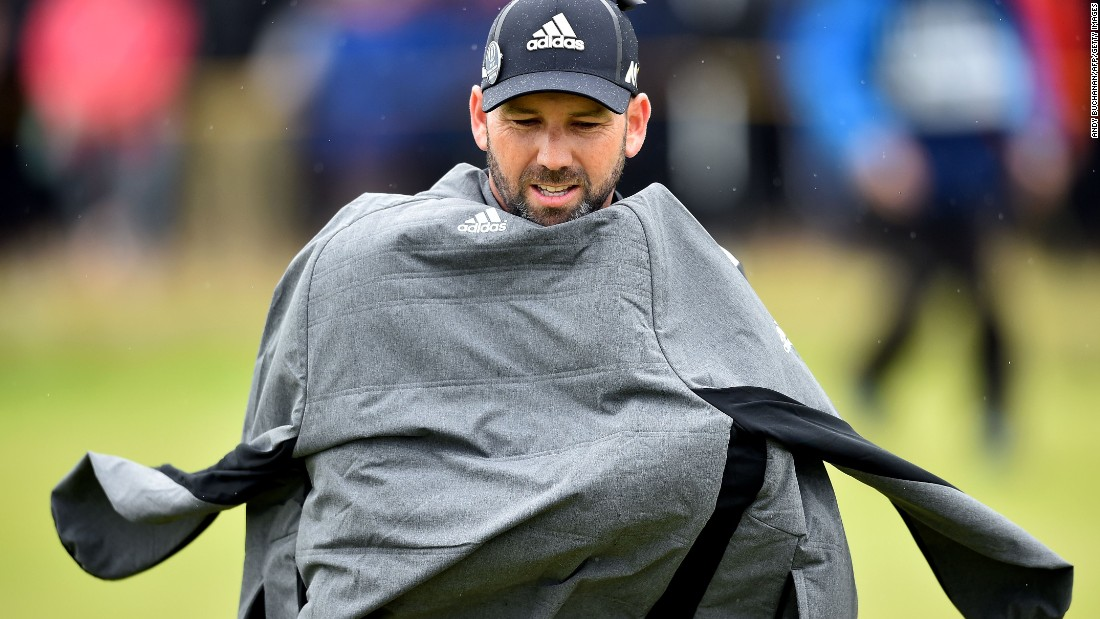 Spain's Sergio Garcia protects himself from the elements during his third round of 73 to go into the clubhouse on 211 -- two under.