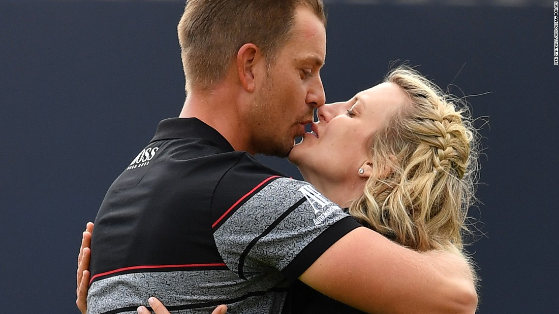 Stenson kisses his wife Emma on the 18th green after sealing his victory and first major.