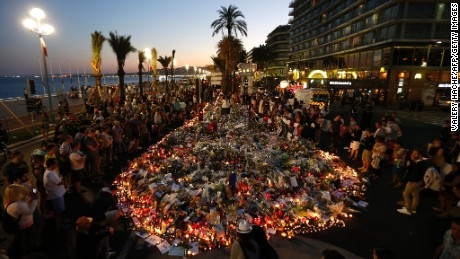 People gather at a makeshift memorial on the Promenade des Anglais in Nice on July 17, 2016, in tribute to the victims of the Bastille Day attack that left 84 dead. The Islamic State group claimed responsibility for the truck attack that killed 84 people in Nice on France's national holiday, a news service affiliated with the jihadists said on July 16. Tunisian Mohamed Lahouaiej-Bouhlel, 31, smashed a 19-tonne truck into a packed crowd of people in the Riviera city celebrating Bastille Day -- France's national day.