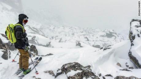 Austin Porzak pauses on a descent. Deep powder and jagged rocks present hurdles.