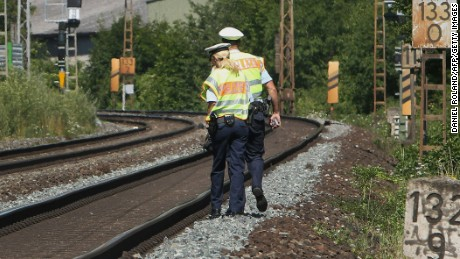 Police officers walk along train tracks in Wuerzburg, southern Germany, on Tuesday, July 19, a day after a man attacked train passengers with an ax.