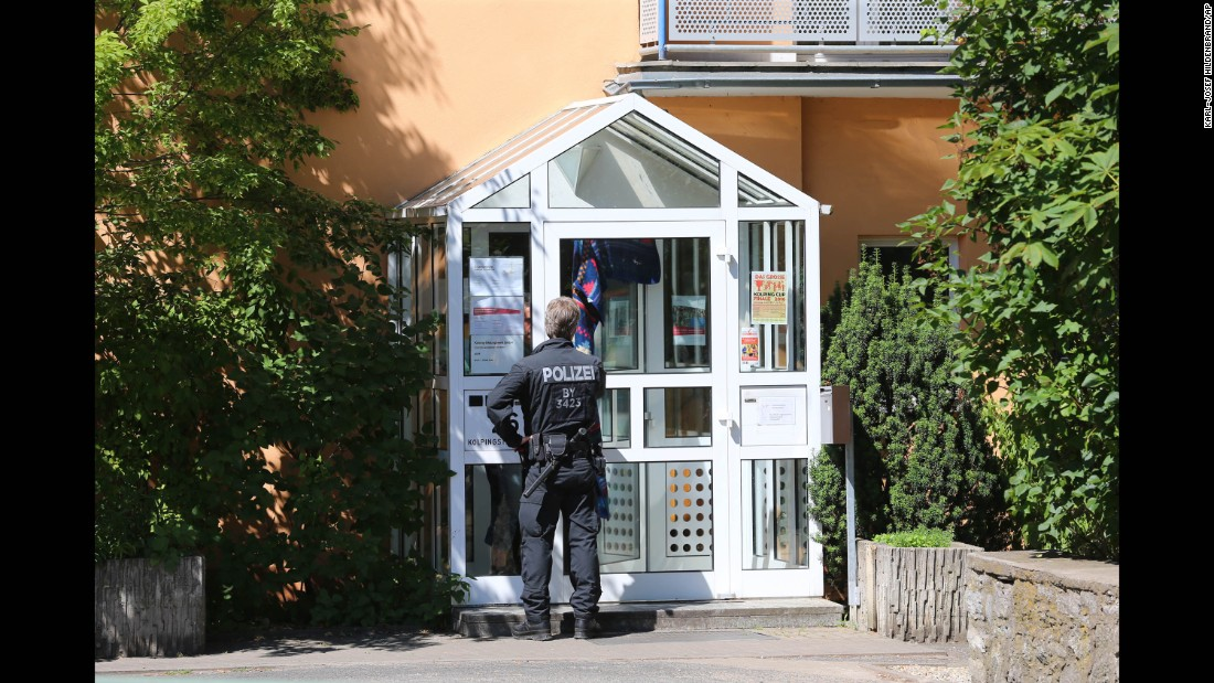 A police officer enters the Kolping House in Ochsenfurt on Tuesday, July 19, where the attacker reportedly lived with other refugees until two weeks ago. The attacker came to Germany without his parents a year ago,  police said.