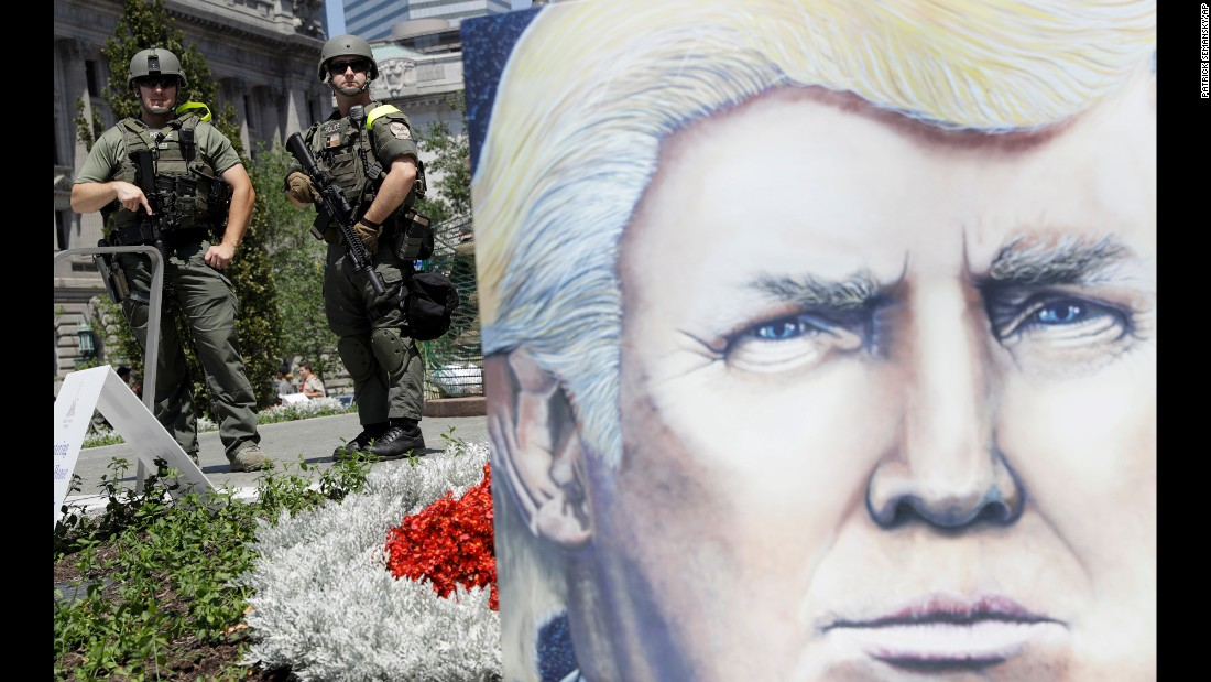 Law enforcement officers stand watch Tuesday in Public Square, near a large poster of Republican presidential candidate Donald Trump.