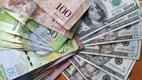 "Picture of US dollars and Venezuelan Bolivares ""fuertes"" (2,15 per dollar) bills in Caracas on August 17, 2009. Venezuelan President Hugo Chavez's government will soon announce new measures to ""restore the currency balance"" which --according to Chavez-- is suffering from a distortion due to an unofficial, though legal, exchange market. AFP PHOTO / Thomas Coex (Photo credit should read THOMAS COEX/AFP/Getty Images)"