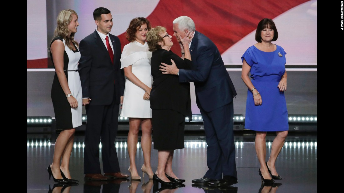 Pence receives a kiss from his mother, Nancy, as his family joins him on stage after his speech.