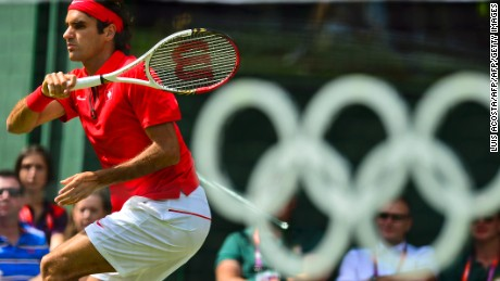 Switzerland's Roger Federer returns the ball to France's Julien Benneteau during their men's single tennis match second round during the London 2012 Olympic Games in London on July 30, 2012.       AFP PHOTO/Luis Acosta        (Photo credit should read LUIS ACOSTA/AFP/GettyImages)