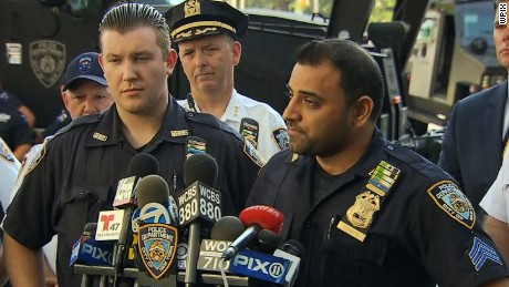 Sgt. Hameed Armani, right, and Officer Peter Cybulski took what they thought was a bomb away to protect the crowds in Times Square.