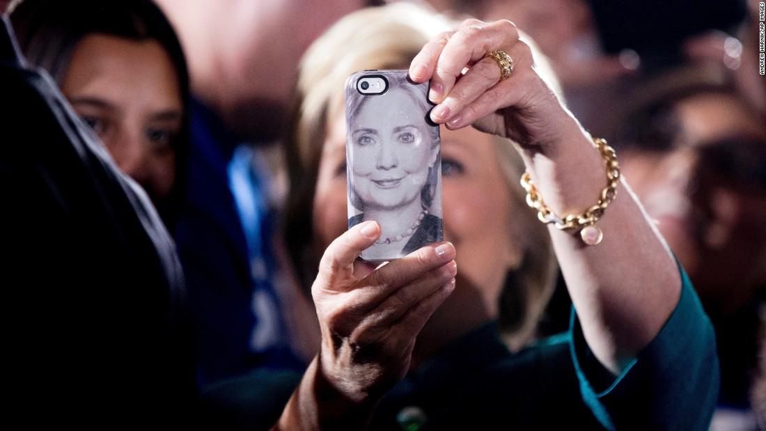Presidential candidate Hillary Clinton uses a phone bearing her likeness as she takes selfies with supporters in Las Vegas on Tuesday, July 19.