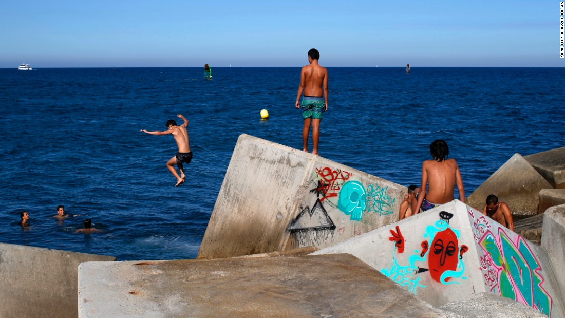 A boy jumps into the sea during a hot day in Barcelona, Spain, on Tuesday, July 19.